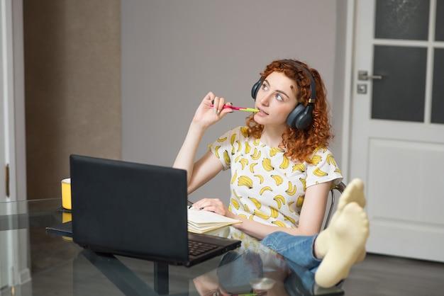 Красивая кавказская девушка в наушниках думает во время работы. работа на дому
