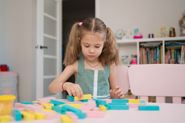 Beautiful caucasian girl playing with wooden multi-colored blocks
