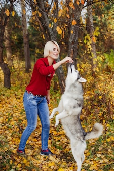 Beautiful caucasian girl plays with husky dog in autumn forest
