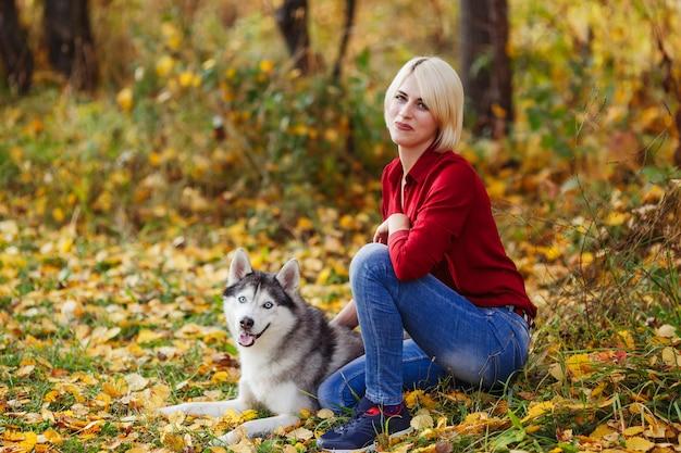 秋の森や公園でハスキー犬と遊ぶ美しい白人少女