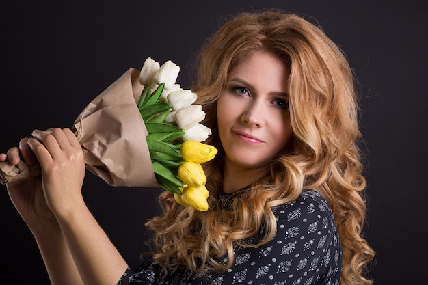 Beautiful caucasian girl posing in studio on black isolated background with bouquet of flowers