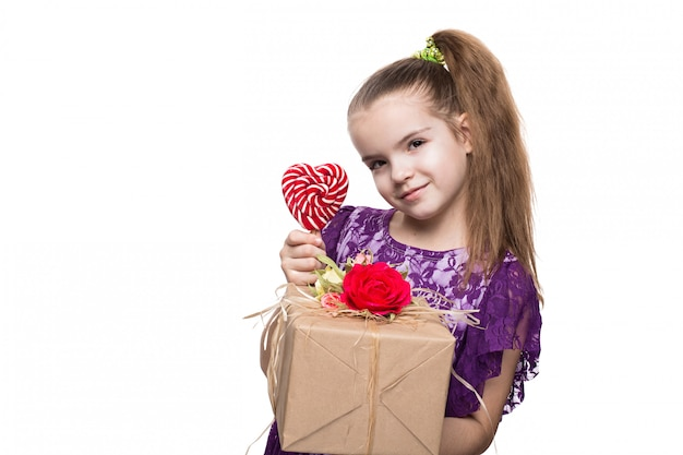 Beautiful caucasian girl in purple lace dress holding a box with a gift decorated with flowers. shooting in studio on isolated white background