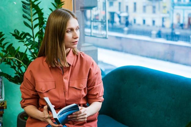 美しい白人の女の子は、本を読んで、見ているソファに座って自宅で彼女の自由な時間を過ごします...