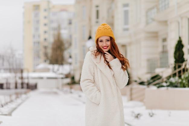 Bella ragazza caucasica che cammina intorno alla città nella giornata invernale. donna felice dello zenzero in camice bianco in posa sulla strada.