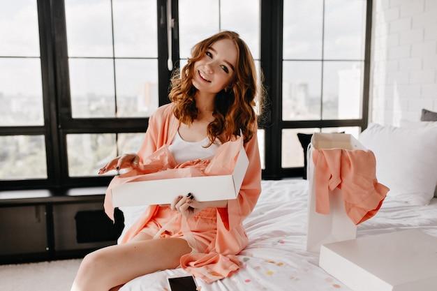 ベッドに座っている巻き毛の美しい白人の女の子。週末の朝を楽しんでいる至福の笑う女性。