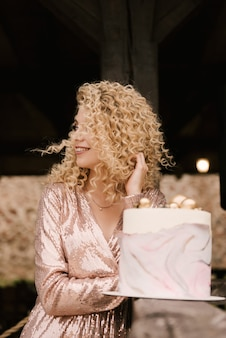 Beautiful caucasian girl with curly hair smiles in honor of her birthday with a festive stylish cake
