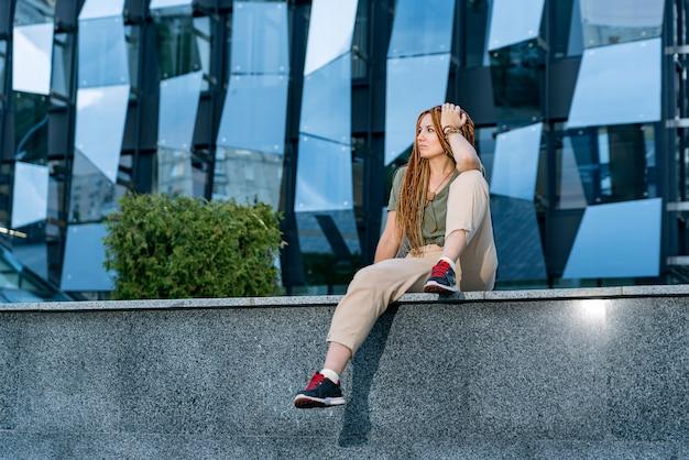 Красивая кавказская девушка с дредами сидит на парапете и смотрит вдаль. серое офисное здание на фоне Premium Фотографии