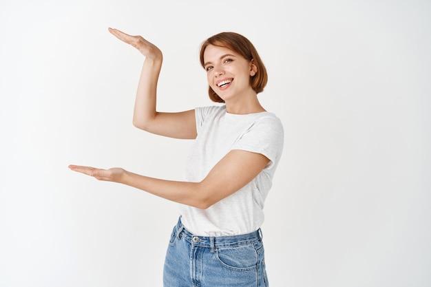 自然な美しさの顔を持つ美しい白人の女の子、コピースペースに大きなサイズのオブジェクトを表示し、手で大きな箱を形作り、白い壁に立っています。