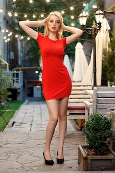 Красивая кавказская девушка с красным макияжем губ в ресторане. красивая сексуальная белокурая женщина в кафе ресторана соблазнительная девушка в красной прическе и макияже платья ест десерт. красота модная стройная модель