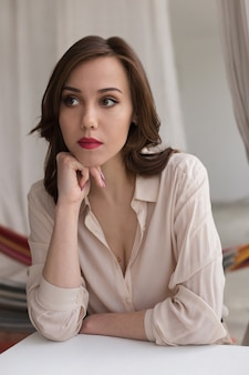 Beautiful caucasian girl with red lips in stylish beige blouse looks thoughtfully aside, leaning on table in cafe.