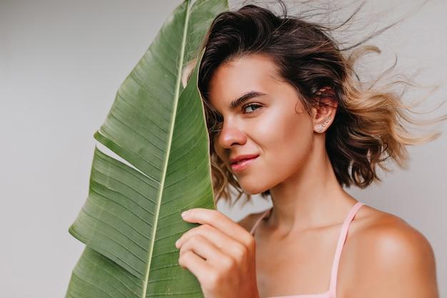 緑の葉で彼女の顔に触れている日焼けした肌を持つ美しい白人の女の子。エキゾチックな植物の後ろに隠れている魅力的な巻き毛の女性モデルの屋内写真。