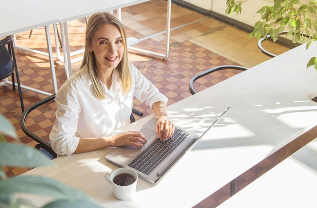 Beautiful caucasian girl working on a laptop remotely in a bright interior.