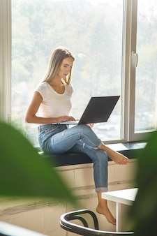 Beautiful caucasian girl working on a laptop sitting on a windowsill in a bright workspace.