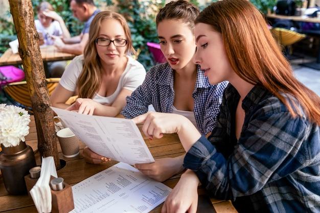 아름다운 백인 소녀는 카페의 테라스에서 메뉴에서 매일 스페셜을 주문하고 있습니다