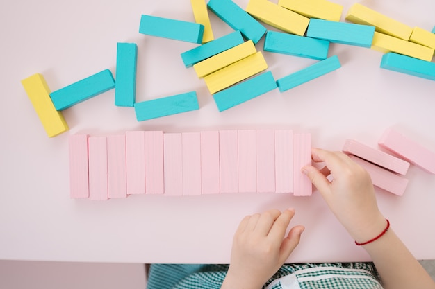 Beautiful caucasian girls playing with wooden multi-colored blocks