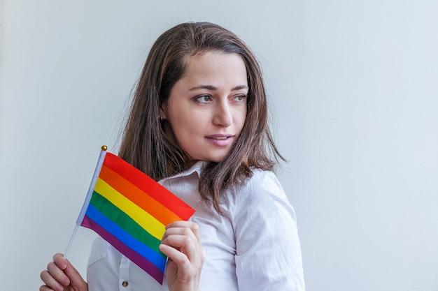Красивая кавказская лесбиянка с радужным флагом лгбт на белом фоне выглядит счастливой и взволнованной.