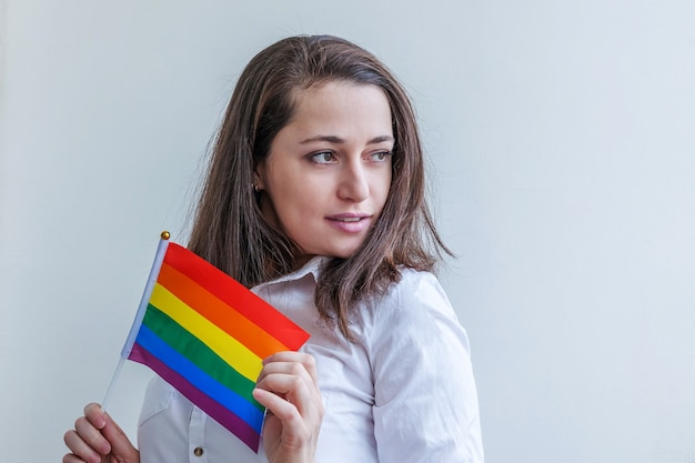 Beautiful caucasian lesbian girl with lgbt rainbow flag isolated on white background looking happy and excited.