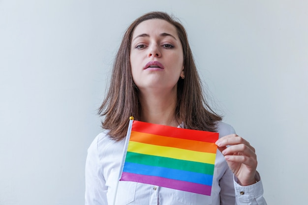 Beautiful caucasian lesbian girl with lgbt rainbow flag isolated on white looking happy and excited. young woman gay pride portrait. equal rights for lgbtq community concept.