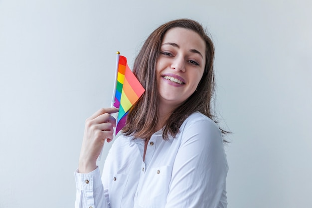 Beautiful caucasian lesbian girl with lgbt rainbow flag isolated on white wall looking happy and excited. young woman gay pride portrait. equal rights for lgbtq community concept.