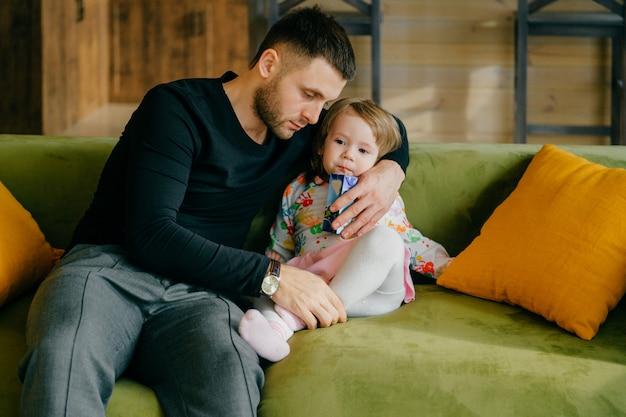 소파에 그의 작은 귀여운 딸을 돌보는 아름다운 백인 남자