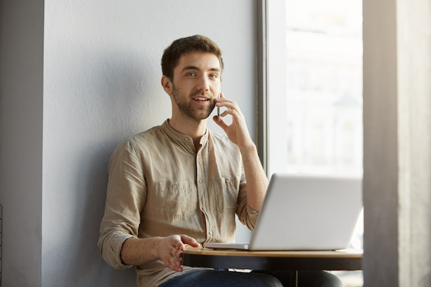 Bello uomo caucasico con i capelli scuri sorrisi, seduto in caffetteria con computer portatile, parlando al telefono e. stile di vita, concetto di business.