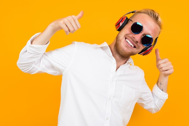 Beautiful caucasian man with glasses listen to music with big red earphones and relax isolated on yellow