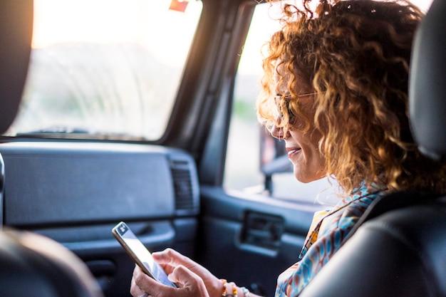 美しい白人の中年女性がスマートフォンを見て、インターネット上のソーシャルメディアをチェックして友達を見つける