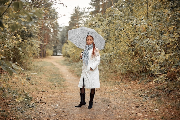 曇りの秋の日に公園で傘を持つ赤い髪の美しい白人の中年女性。