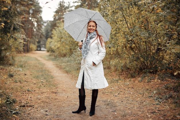 曇りの秋の日に公園で傘を持つ赤い髪の美しい白人の中年女性。 Premium写真
