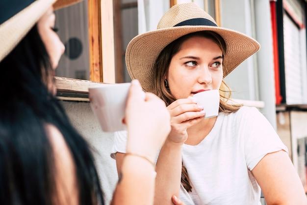 美しい白人モデルが実際のシーンで後ろから見た友人とバーでコーヒーを飲む