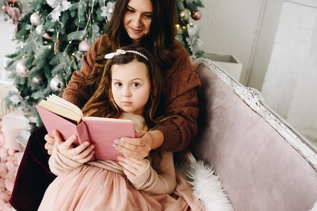 Beautiful caucasian moher sitting with her lovely little daughter reading purple book near decorated christmas tree