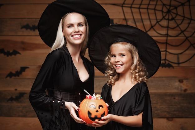 美しいコーカサス人の母親と彼女の娘の魔女の衣装ハロウィーンのお菓子を共有してハロウィンを祝う