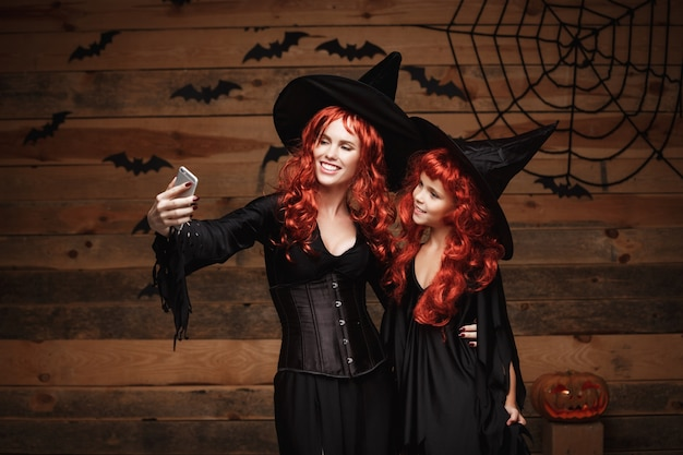 Beautiful caucasian mother and her daughter with long red hair in witch costumes taking a selfie