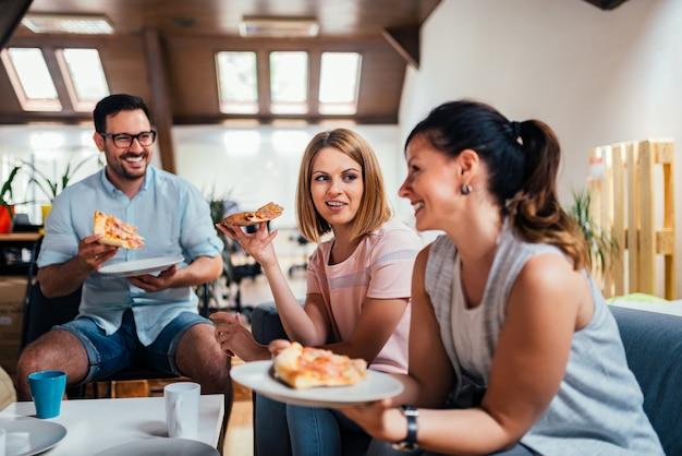 Beautiful caucasian people having pizza indoors.