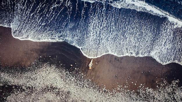Красивая модель кавказских людей на песчаном пляже на тенерифе ловит солнце, когда к ней приближается большая волна. отпуск воздушная концепция с дроном. медитация и радость для самостоятельного образа жизни