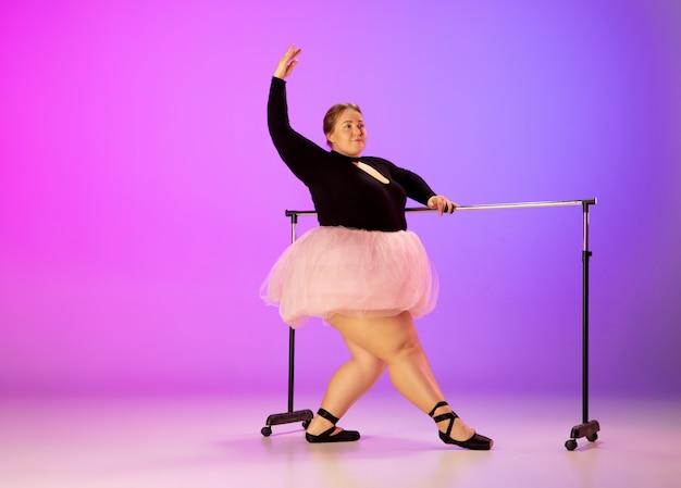 ネオンの光の中でグラデーション紫ピンクのスタジオの背景にバレエダンスを練習する美しい白人プラスサイズのモデル。モチベーション、インクルージョン、夢と成果の概念。バレリーナになる価値があります。