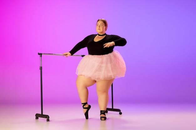 아름다운 백인 플러스 사이즈 모델은 네온 불빛 아래 그라데이션 보라색-분홍색 스튜디오 배경에서 발레 댄스를 연습합니다. 동기 부여, 포함, 꿈 및 성취의 개념. 발레리나가 될 가치가 있습니다.