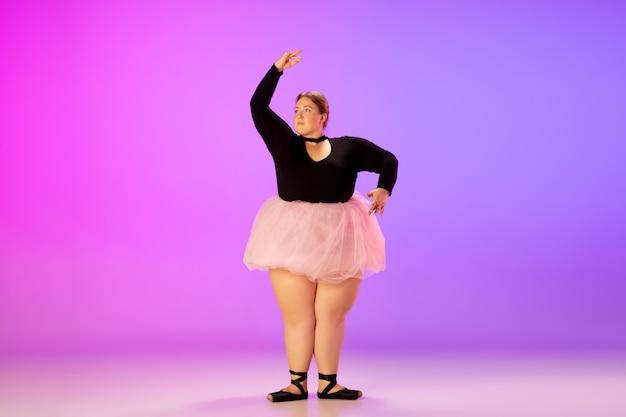 グラデーションでバレエダンスを練習する美しい白人プラスサイズモデル