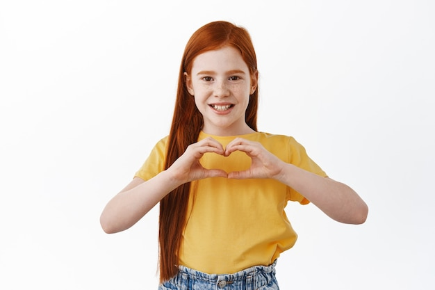 Beautiful caucasian redhead little girl, kid with red hair and freckles shows i love you, heart sign and smiles adorable at front, white wall