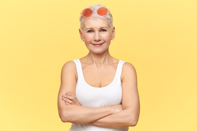 Beautiful caucasian retired woman wearing round pink sunglasses and white tank top, crossing arms on her chest, having confident facial expression.