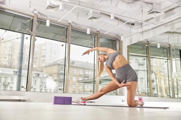 아름 다운 백인 슬림 여자는 빛 현대 스튜디오에서 스트레칭 훈련을하고있다