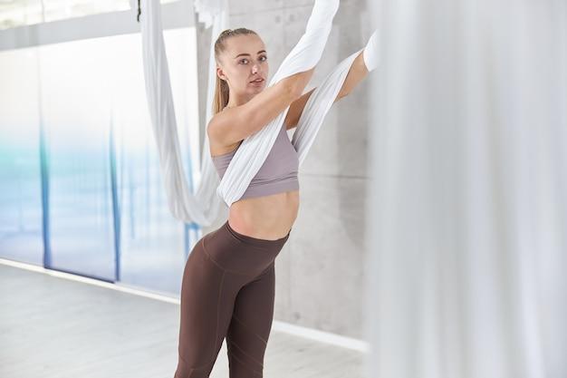 Beautiful caucasian slim woman is doing stretching training in light modern studio