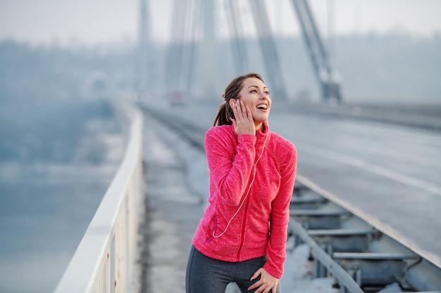 橋の上に立っている間休んでいると音楽を聴くスポーツウェアの美しい白人笑顔ブルネット。冬。屋外フィットネス。