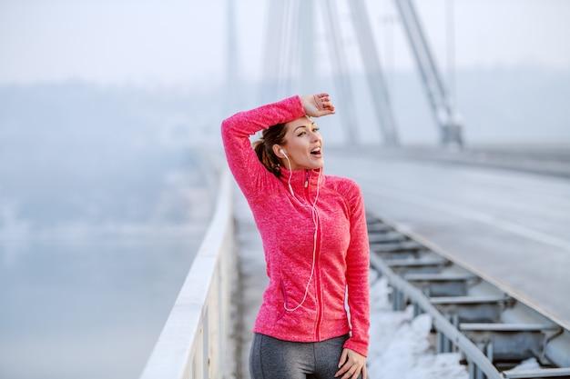 橋の上に立っている間休憩、額から汗をかき、音楽を聴くスポーツウェアで美しい白人笑顔ブルネット。冬。屋外フィットネス。