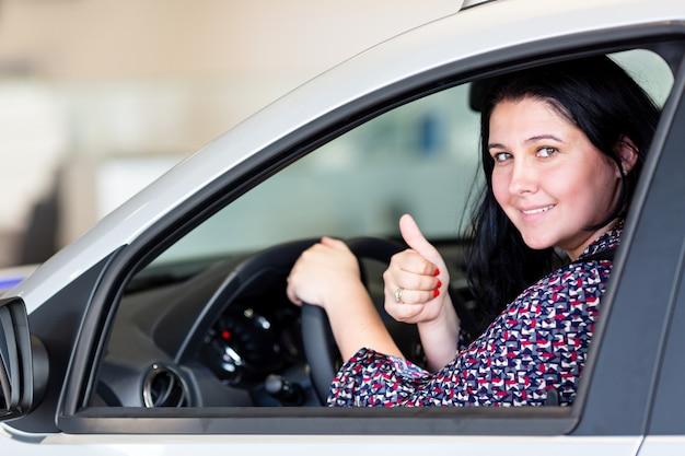 Красивая кавказская усмехаясь женщина брюнет сидя в новом автомобиле и показывая большие пальцы руки вверх.