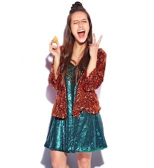 Modello castana sorridente caucasico bello della donna dei pantaloni a vita bassa in rivestimento alla moda di estate di riflessione shinny luminosa e vestito verde isolati. mangiando amaretto francese e mostrando il segno di pace