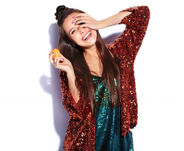 Beautiful caucasian smiling hipster brunette woman model in bright shinny reflecting summer stylish jacket and green dress isolated . eating french macaroon