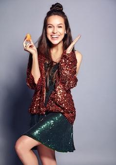 Красивая кавказская усмехаясь модель женщины брюнет битника в яркой shinny отражая куртке лета стильной и зеленом платье представляя на сером цвете. еда французского макаруна