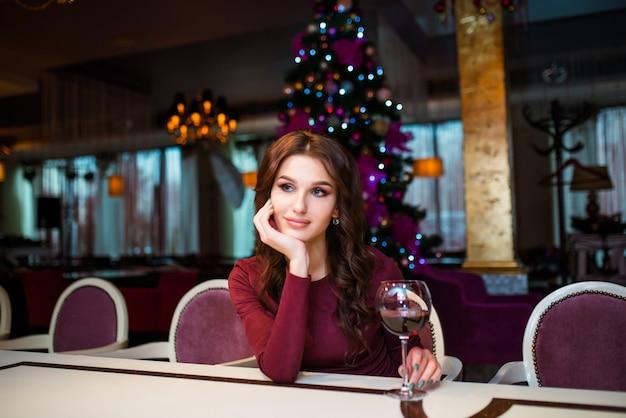 Красивая кавказская улыбающаяся молодая счастливая женщина в красном платье, рождественской шляпе и гирлянде мишуры, стоящей с бокалом шампанского на белом фоне. изолированная девушка санты. концепция праздника новый год.