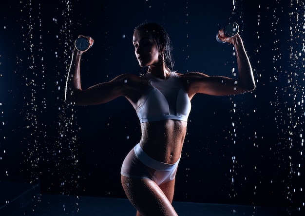 Beautiful caucasian sportswoman posing with dumbbells on a black background in spray of water.